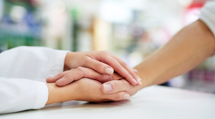 pharmacist holding patient hand