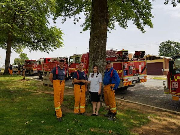 Helen Feng, owner of the Alliance Pharmacy in Tallangatta, VIC, with members of the local Country Fire Authority crew. Photo: supplied.