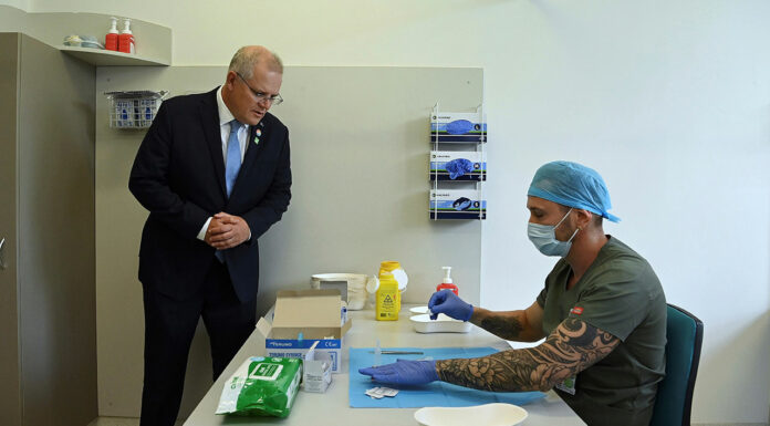 Prime Minister Scott Morrison looks on as pharmacist Branko Radojkovic prepares a simulation of the COVID-19 vaccine at Sydney's Royal Prince Alfred Hospital last week