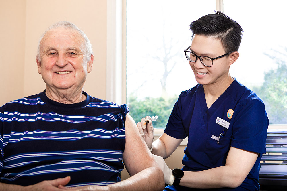 general practice pharmacist Zachary Sum MPS vaccinating a patient.
